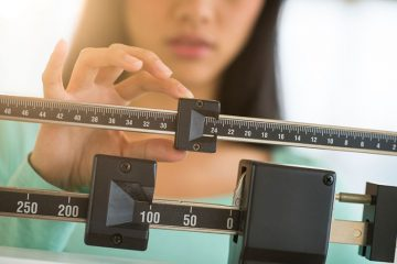 Woman Checking Her Weight If She's Overweight