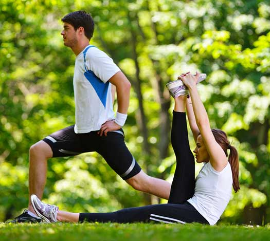 couples stretching after exercise outdoors