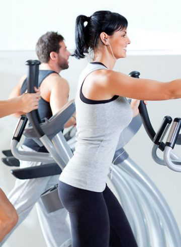 Men and woman with compact elliptical machines
