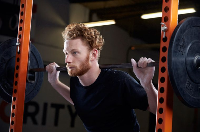 Man lifting weights and using squat rack