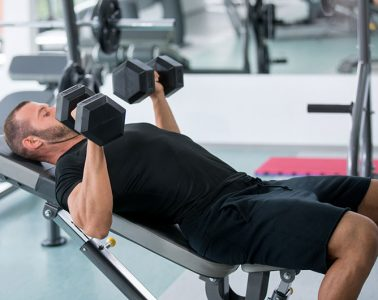 Man lifting dumbbells while laying on weight bench
