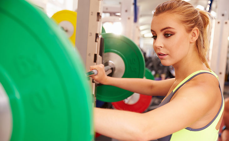Woman choosing which squat rack to use
