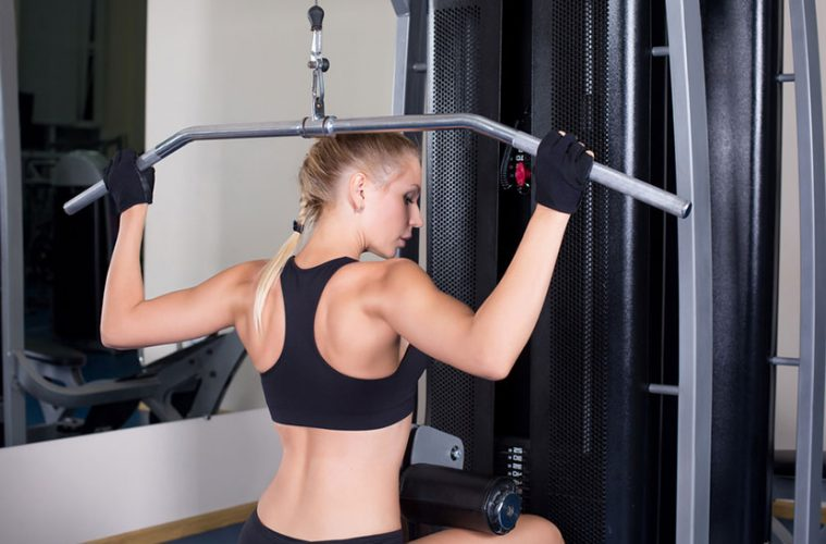 Woman using a lat pulldown machine at home.