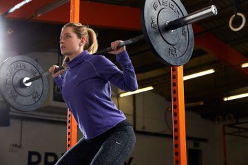 Woman lifting wrights and using squat rack
