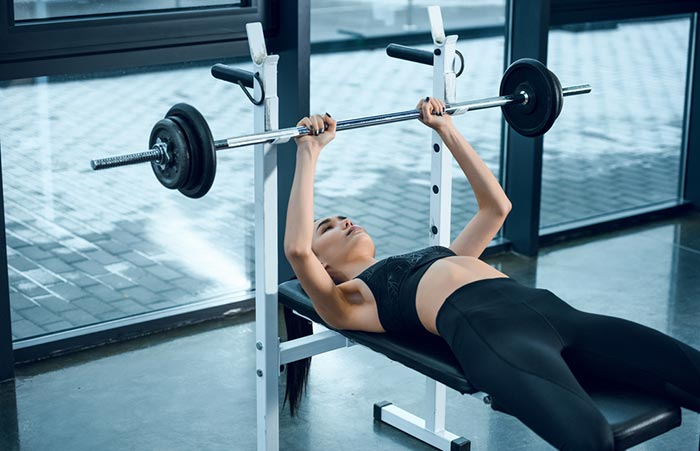 Woman lifting while laying on weight bench