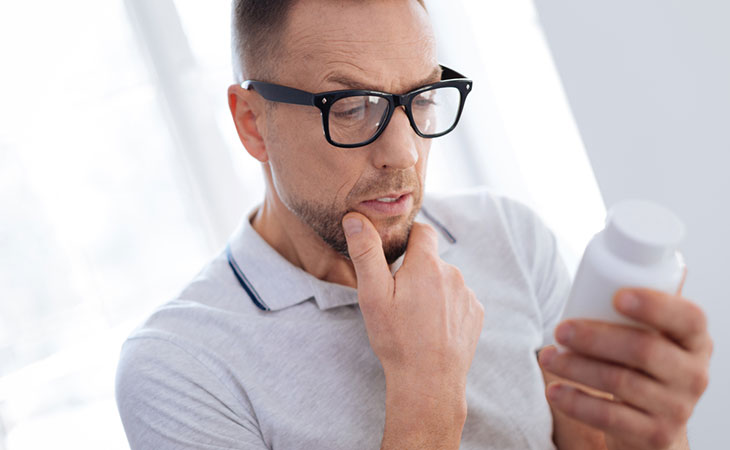 Man thoughtfully reading the ingredients of the supplements
