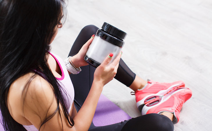 Woman Reading Important Ingredients in Pre-Workout Supplements