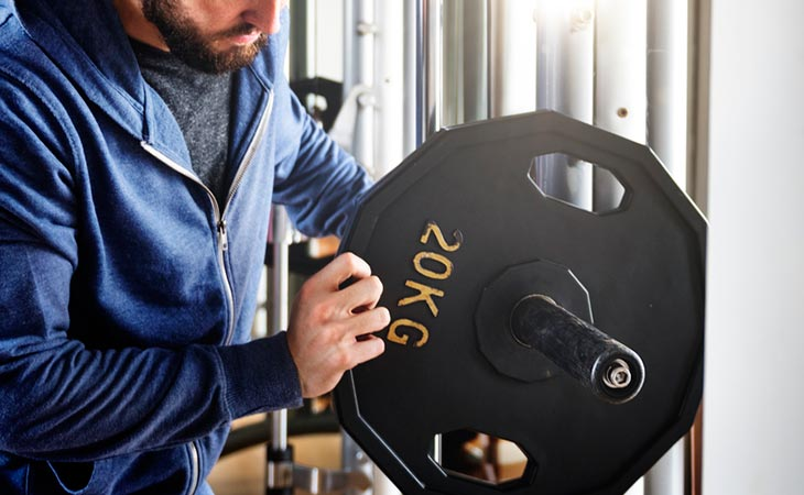 Man Choosing Weight Plates For His Barbell