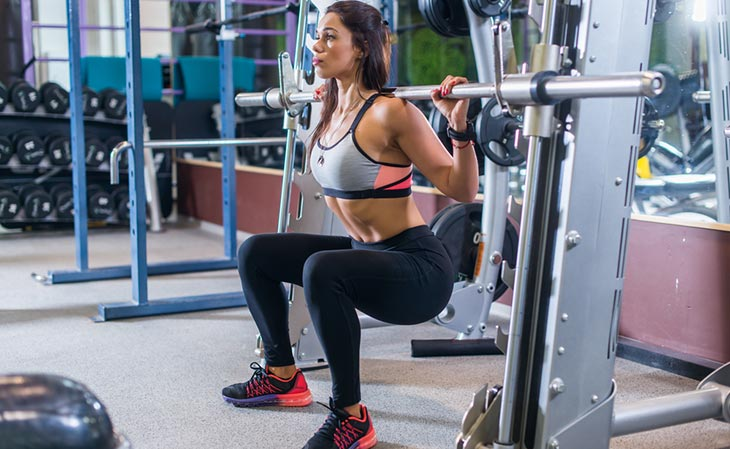 Woman Using A Smith Assisted Squat Machine