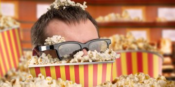 Man with eyeglasses in a bucket full of popcorn