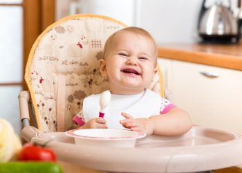 A happy baby sitting on a high chair holding a spoon