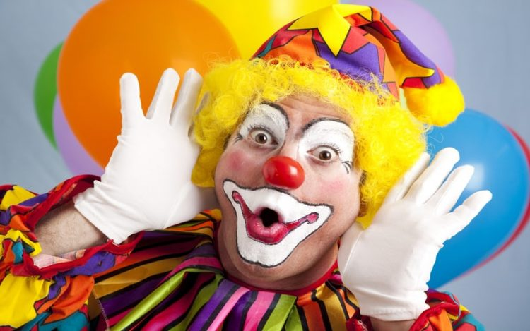 A colorful clown with a red nose